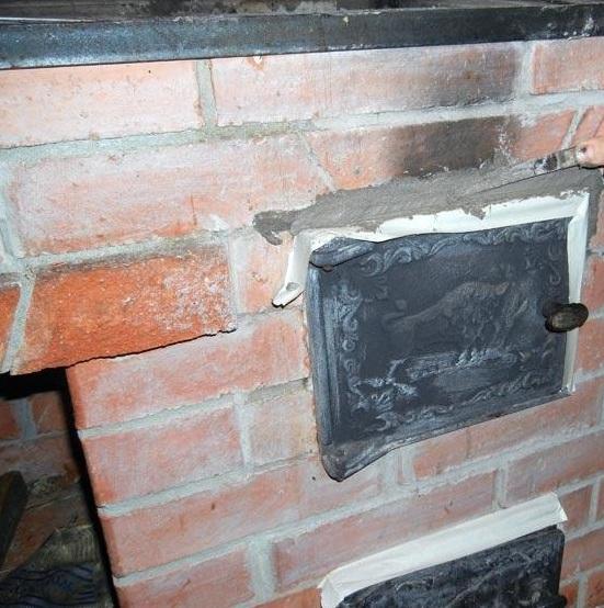 Нанесение раствора при ремонте на щель между между дверцей и кладкой